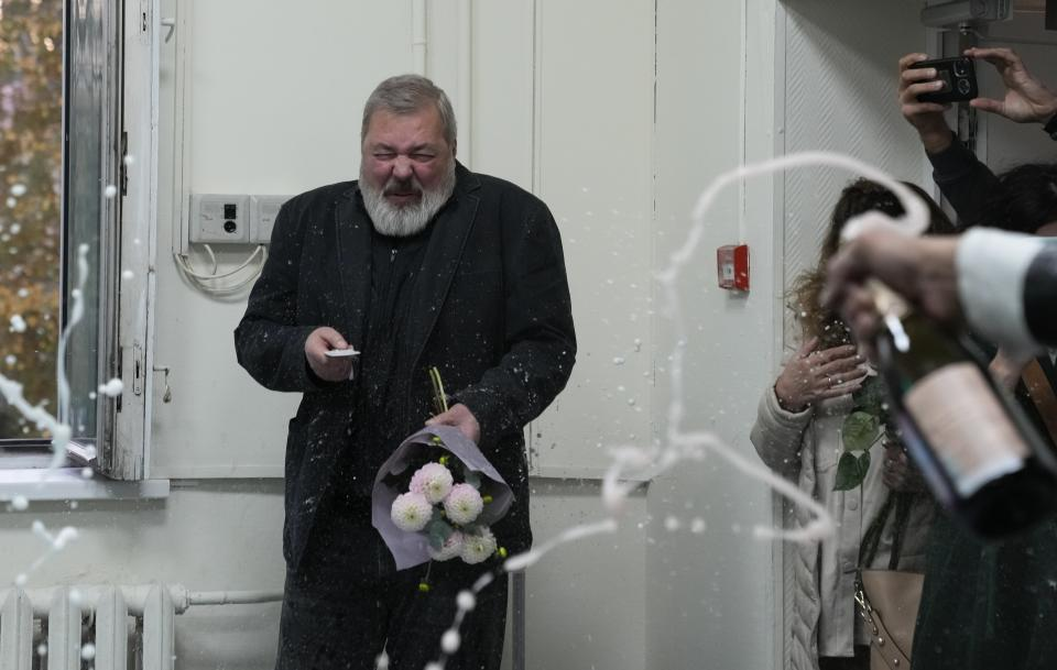 Colleagues pour champaign on Novaya Gazeta editor Dmitry Muratov at the Novaya Gazeta newspaper, in Moscow, Russia, Friday, Oct. 8, 2021. As a new Nobel Peace Prize laureate, Russian newspaper editor Dmitry Muratov has downplayed the buzz around his name. The award isn't for him, he says, but for all of the staff at Novaya Gazeta, the independent Russian newspaper noted for investigations of official corruption, human rights abuses and Kremlin criticism. (AP Photo/Alexander Zemlianichenko)
