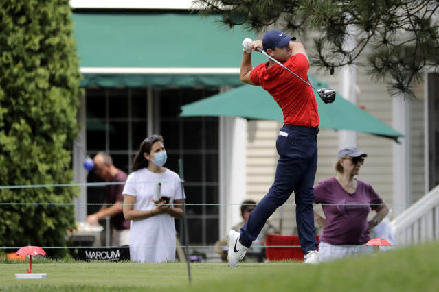 People are seen in the backyard of a home as Rory McIlroy, of Northern Ireland, tees off on the sixth hole during the final round of the Travelers Championship golf tournament at TPC River Highlands, Sunday, June 28, 2020, in Cromwell, Conn. (AP Photo/Frank Franklin II)