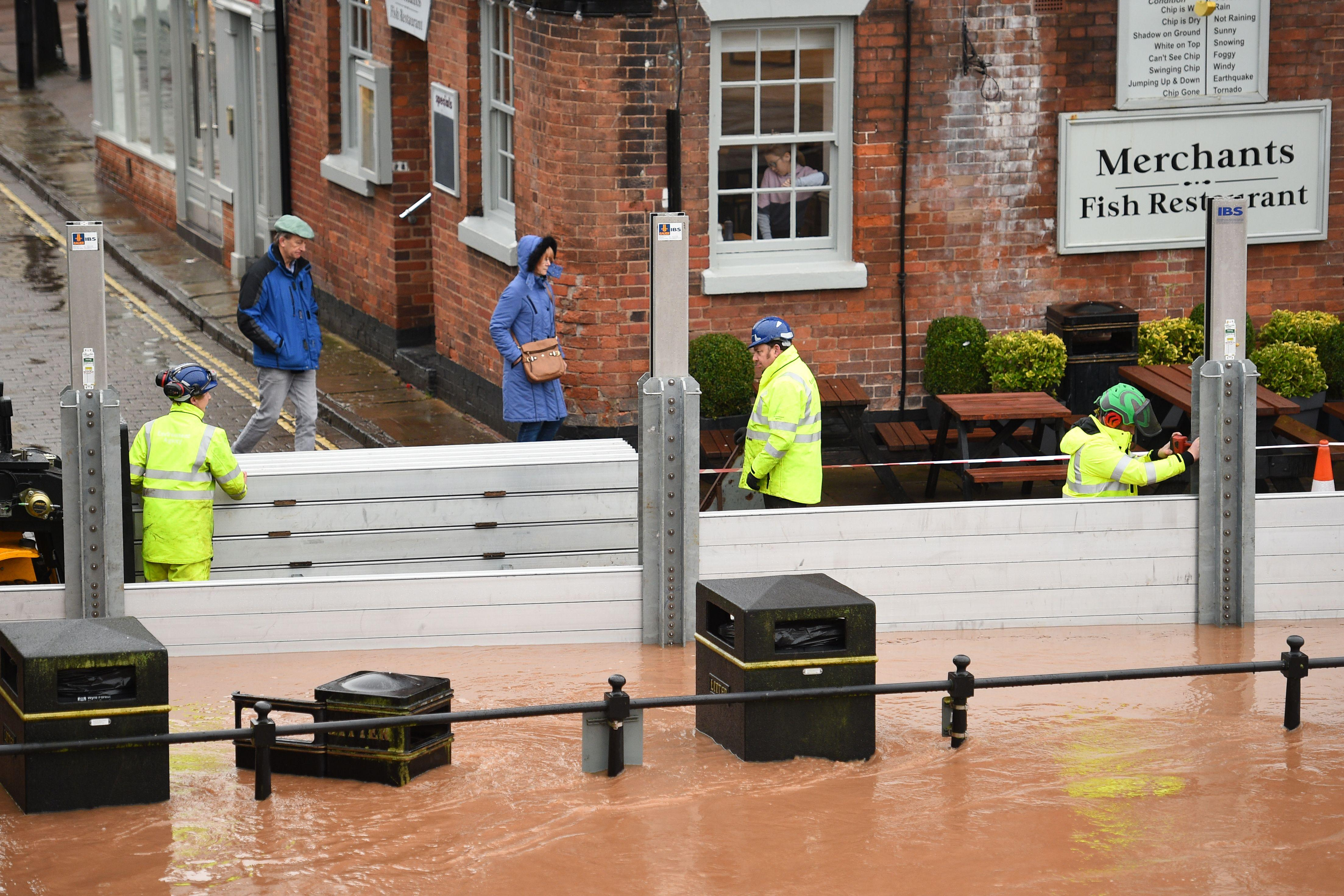 """Environment agency workers put up flood defences in floodwater after the River Severn bursts it's banks in Bewdley, west of Birmingham on February 16, 2020, after Storm Dennis caused flooding across large swathes of Britain. - As Storm Dennis sweeps in, the country is bracing itself for widespread weather disruption for the second weekend in a row. Experts have warned that conditions amount to a """"perfect storm"""", with hundreds of homes at risk of flooding. (Photo by Oli SCARFF / AFP) (Photo by OLI SCARFF/AFP via Getty Images)"""