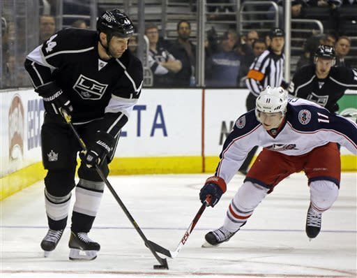Los Angeles Kings defenseman Robyn Regehr (44) and Columbus Blue Jackets left wing Matt Calvert (11) battle for the puck in the first period of an NHL hockey game in Los Angeles, Thursday, April 18, 2013. (AP Photo/Reed Saxon)