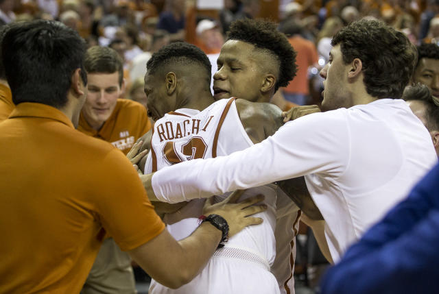 Texas guard Jacob Young (3) hugs guard Kerwin Roach II (12) after Roach made the game-winning shot to defeat Oklahoma State 65-64 in an NCAA college basketball game in Austin, Texas, on Saturday, Feb. 24, 2018. (Nick Wagner /Austin American-Statesman via AP)
