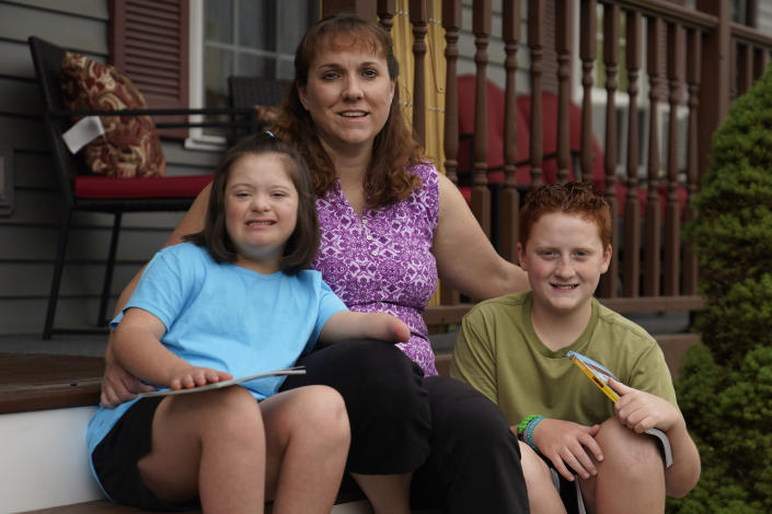 Jennifer Osgood, center, poses with her children Lily, 7, left, and Noah, 12, right, at their home in Fairfax, Vt., on Tuesday, July 20, 2021. The Osgood children will continued to be homeschool this upcoming school year. As the pandemic took hold across the United States in the spring of 2020, it brought disruption and anxiety to most families. Yet some parents are grateful for one consequence: they are now opting to homeschool their children even as schools plan to resume in-person classes. (AP Photo/Charles Krupa)