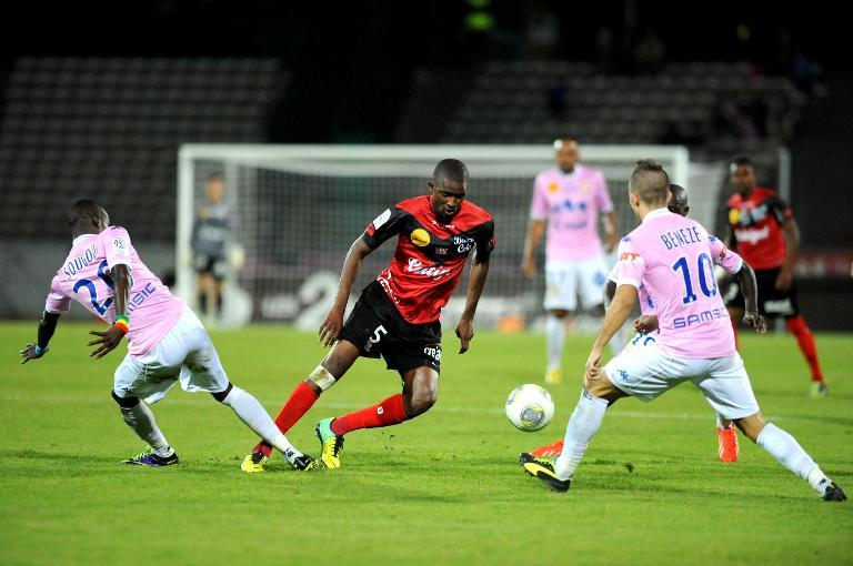 Evian forward Modou Sougou (L) vies with Guingamp midfielder Moustapha Diallo (C) during their French Liggue 1 match at the city stadium in Annecy, eastern France on on October 19, 2013