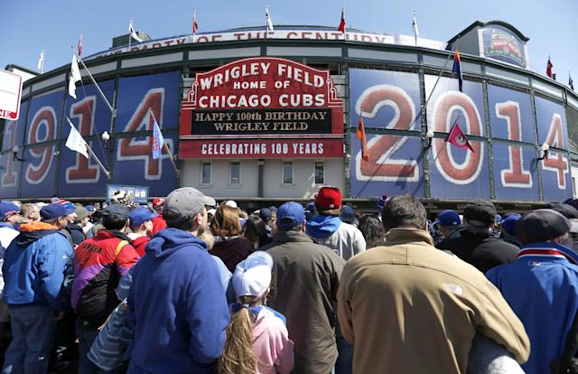 Baseball fans wait to enter Wrigley Field on the 100th anniversary of the first baseball game at the park, before a game between the Arizona Diamondbacks and Chicago Cubs, Wednesday, April 23, 2014, in Chicago. (AP Photo/Charles Rex Arbogast)