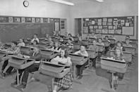 <p>A classroom of students is excited to try out their new desks, which could be adjusted to be flat or sloped.</p>