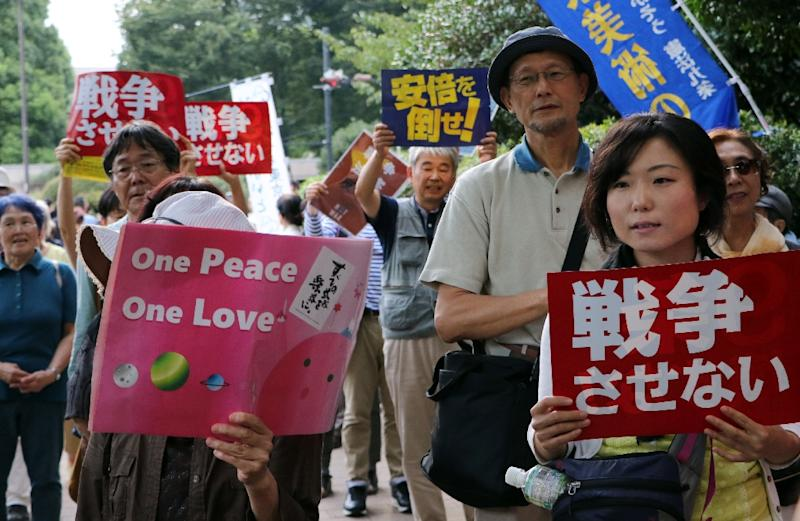 People hold placards to protest against Japan's Prime Minister Shinzo Abe's controversial security bills near the National Diet in Tokyo on September 19, 2015 (AFP Photo/Yoshikazu Tsuno)