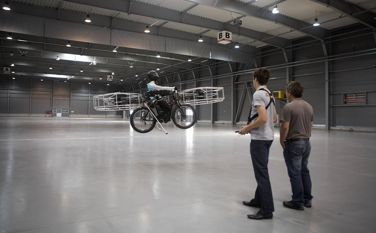 A technician operates by remote control 'Flying bike' bicycle ahead of its first public flight on June 12, 2013 in Prague, Czech Republic. The bike has been manufactured by 3 different companies from the Czech Republic (Duratec, Technodat, Evektor) and has been supported by French Company Dassault System. The F-Bike has four main motors (10kW) and two stabilization motors (3,5 kW). It has an estimated constant flight time of 3-5 minutes.  (Photo by Matej Divizna/Getty Images)
