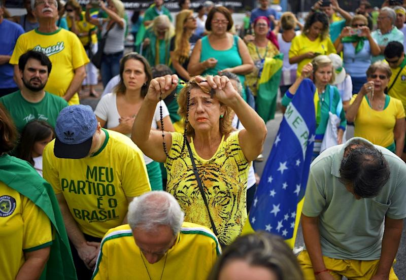 A supporter of Brazilian President Jair Bolsonaro prays during a demonstration to shore up his unltraconservative government as it faces growing opposition (AFP Photo/Carl DE SOUZA)