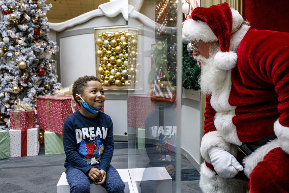 Kashden Dunlap, of Enola, visits with Santa Claus, with safety protocols in place, at Capital City Mall in Lower Allen Township, Pa., on Wednesday, Nov. 11, 2020. Malls are doing all they can to keep the jolly old man safe from the coronavirus, including banning kids from sitting on his knee, completely changing what a Santa visit looks like. (Dan Gleiter/The Patriot-News via AP)