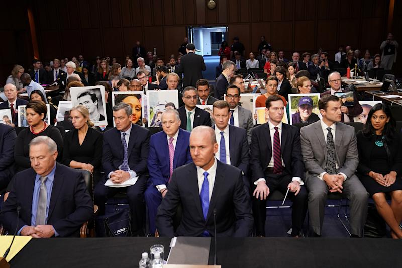 """Boeing Chief Executive Dennis Muilenburg sits in front of family members holding photographs of Boeing 737 MAX crash victims from two deadly 737 MAX crashes that killed 346 people as Muilenburg waits to testify before a Senate Commerce, Science and Transportation Committee hearing on """"aviation safety"""" and the grounded 737 MAX on Capitol Hill in Washington, U.S., October 29, 2019. REUTERS/Sarah Silbiger"""