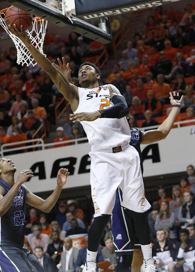 Oklahoma State's Le'Bryan Nash (2) shoots between TCU guard Jarvis Ray (22) and forward Amric Fields during the second half of an NCAA college basketball game in Stillwater, Okla., Wednesday, Jan. 15, 2014. Oklahoma State won 82-50. (AP Photo/Sue Ogrocki)