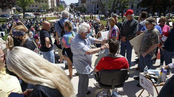 PHOTO: Owosso barber, Karl Manke, gives a free haircut to Parker Shonts, of Lake Orion, on the steps of the state Capitol during Operation Haircut on May 20, 2020 in Lansing, Michigan. (Elaine Cromie/Getty Images)