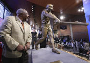 FILE- In this March 29, 2017, file photo, Hank Aaron looks at his new statue in Monument Garden at SunTrust Park, home of the Atlanta Braves, after the unveiling ceremony in Atlanta. Hank Aaron, who endured racist threats with stoic dignity during his pursuit of Babe Ruth but went on to break the career home run record in the pre-steroids era, died early Friday, Jan. 22, 2021. He was 86. The Atlanta Braves said Aaron died peacefully in his sleep. No cause of death was given. (Curtis Compton/Atlanta Journal-Constitution via AP, File)