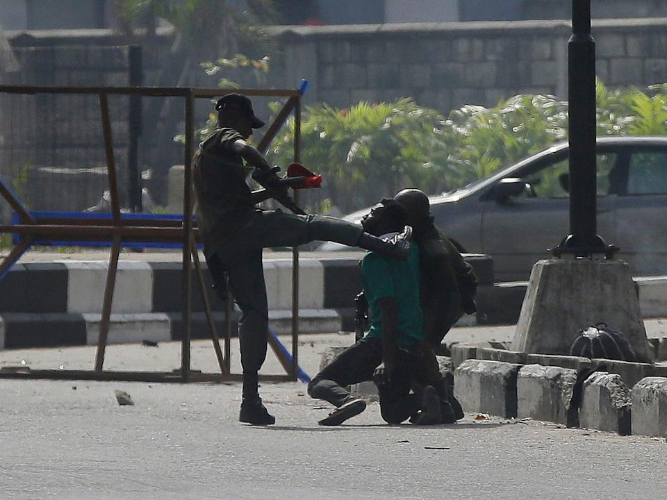 <p>Nigerian security officer kicking protester in Lagos</p> (AP)