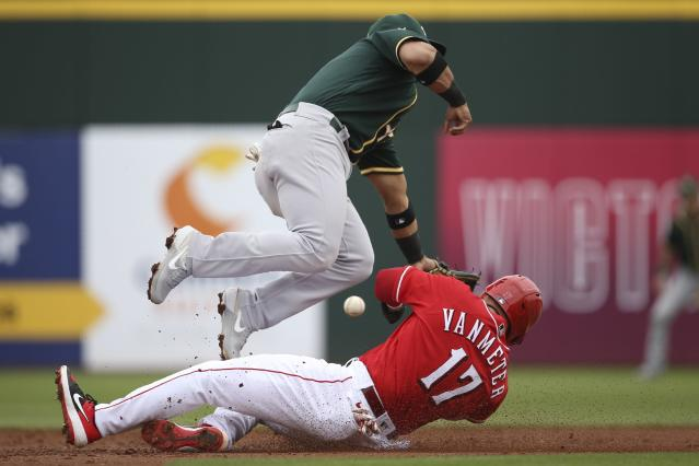 Cincinnati Reds' Josh VanMeter (17) steals second base as he collides with Oakland Athletics second baseman Franklin Barreto, top, as the ball skips between both players during the second inning of a spring training baseball game Friday, Feb. 28, 2020, in Goodyear, Ariz. (AP Photo/Ross D. Franklin)