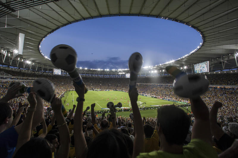 In this photo taken June 2, 2013, fans celebrate after Brazil scored against England during a friendly soccer game at the Maracana stadium, in Rio de Janeiro, Brazil. The Confederations Cup will be a test both on and off the field for Brazil. The country is trying to show that it can build stadiums and complete infrastructure projects in time for the 2014 World Cup, and the national team will try to show that is has the potential to contend for its sixth world title. (AP Photo/Felipe Dana)