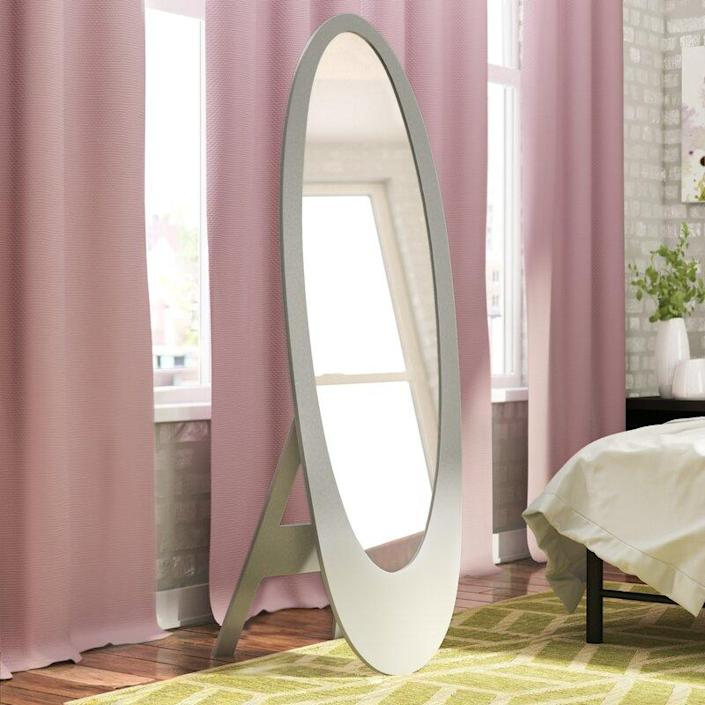"""Seventies home decor fans, rejoice! This mirror is perfect for your funky retro space. Pair this with a patterned upholstered armchair, flared jeans, and your favorite tinted sunglasses, and you're good to go. $250, Wayfair. <a href=""""https://www.wayfair.com/decor-pillows/pdp/wade-logan-trigg-contemporary-oval-cheval-mirror-wdln4048.html?piid="""" rel=""""nofollow noopener"""" target=""""_blank"""" data-ylk=""""slk:Get it now!"""" class=""""link rapid-noclick-resp"""">Get it now!</a>"""