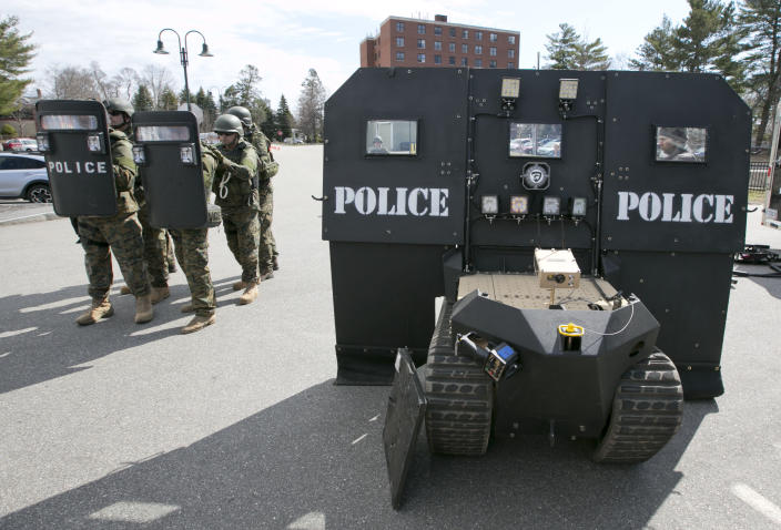 """A team of police line up behind a pair of hand-held bulletproof shields, showing the relative lack of protection compared to a SWAT robot, right, during a demonstration for the media in Sanford, Maine on Thursday, April 18, 2013. Michael and Geoff Howe say their """"SWAT robot"""" keeps SWAT teams and other first responders safe in standoffs and while confronting armed suspects. (AP Photo/Robert F. Bukaty)"""