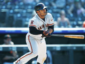 San Francisco Giants' Donovan Solano follows the flight of his RBI-double off Colorado Rockies relief pitcher Chad Bettis in the eighth inning of a baseball game Wednesday, July 17, 2019, in Denver. (AP Photo/David Zalubowski)