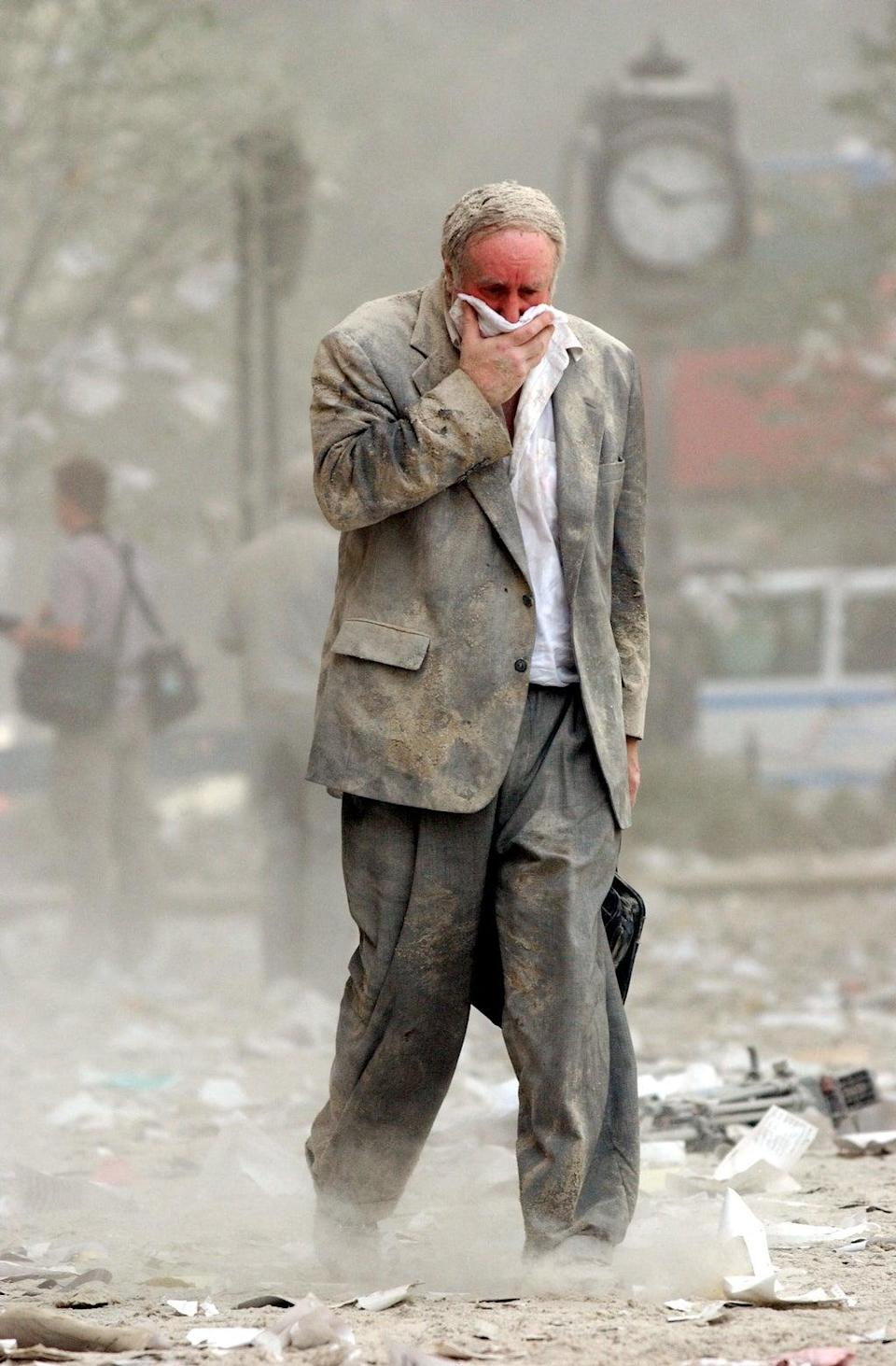 Survivor Edward Fine, who was on the 79th floor of the North Tower when it was struck, covers his mouth as he walks through the debris (AFP/Getty)