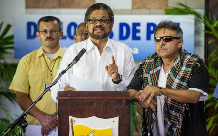 The Commander of the FARC-EP leftist guerrillas Ivan Marquez reads a statement next to Commander Jesus Santrich in Havana for the peace talks with the Colombian government, on August 22, 2014 (AFP Photo/Yamil Lage)