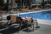 A German tourist takes a sunbath at the Riu Concordia hotel swimming pool in Palma de Mallorca, Spain, Monday, June 15, 2020. Whether its German holidaymakers basking in Spain's sunshine or Parisians renewing their love affair with their city, Monday's border openings and further scrapping of restrictions offered Europeans a taste of pre-coronavirus life that they may have taken for granted. (AP Photo/Joan Mateu)