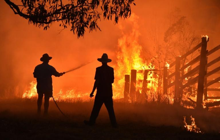 Residents defend a property from a bushfire at Hillsville near Taree, 350km north of Sydney