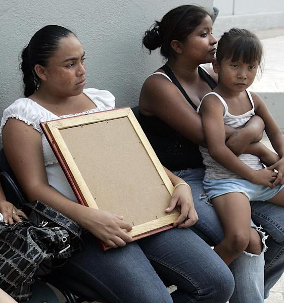 Relatives and family members hold a picture of their father who was killed in the Pemex gas explosion on Tuesday, while waiting for word at the PGR facility in Reynosa, Mexico, Wednesday, Sept. 19, 2012. (AP Photo/The Monitor, Delcia Lopez)