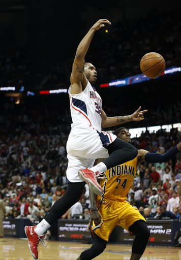 Atlanta Hawks forward Mike Scott (32) is fouled by Indiana Pacers forward Paul George (24) as he drives to the basket in the second half of Game 4 of an NBA basketball first-round playoff series, Saturday, April 26, 2014, in Atlanta. The Pacers won 91-88 to even the series at two games apiece. (AP Photo/John Bazemore)