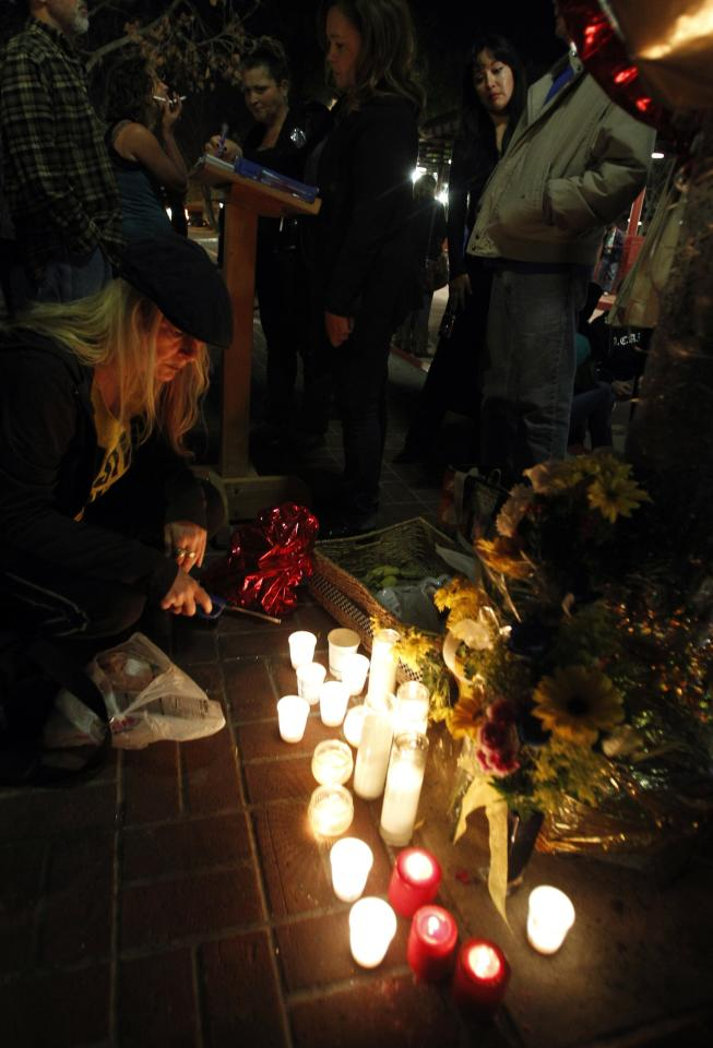Chryss O'Raidy of Norwalk, California lights candles at a makeshift memorial site for Kelly Thomas at the bus terminal in Fullerton, California January 13, 2014. Ex-Fullerton police officers Manuel Ramos and Jay Cicinelli were acquitted on Monday following a month-long trial, in the 2011 beating and stun-gun death of 37-year-old mentally ill California homeless man Thomas that touched off street protests and political upheaval in the Los Angeles suburb of Fullerton. REUTERS/Alex Gallardo (UNITED STATES - Tags: CRIME LAW)