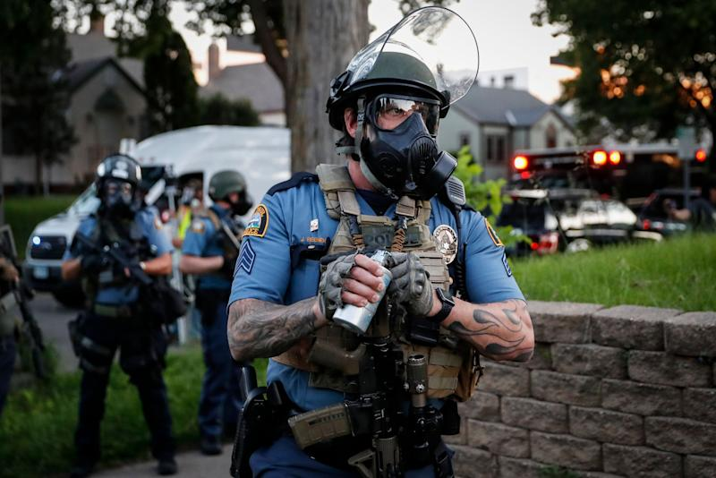 <strong>A police officer prepares to throw a tear gas canister towards protestors on Thursday.</strong> (Photo: ASSOCIATED PRESS)
