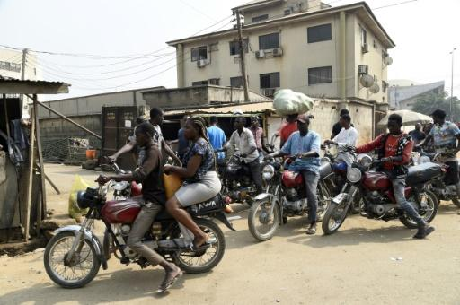 A lady rides on the back of a motorbike taxi in Lagos despite a ban on their use