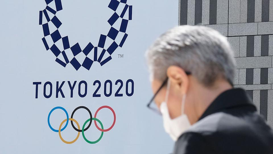 Pictured here, a Tokyo local wears a face mask walking near a sign for the Olympic Games.