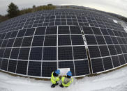 Electricians Zach Newton and Bryan Driscoll consult a wiring schematic while installing solar panels at the 38-acre BNRG/Dirigo solar farm, Thursday, Jan. 14, 2021, in Oxford, Maine. President Joe Biden wants to change the way the U.S. uses energy by expanding renewables, but faces several challenges.. (AP Photo/Robert F. Bukaty)