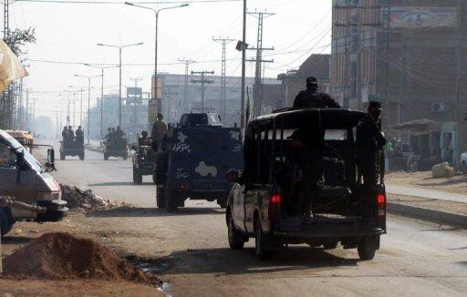 This file photo shows Pakistani soldiers and police patrolling a street in Bannu, in 2011. Nearly 400 prisoners including militants escaped from a jail in northwestern Pakistan after an attack by insurgents armed with guns, grenades and rockets
