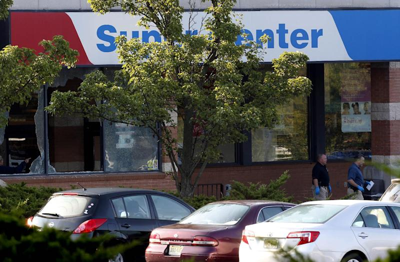 Officials investigate the scene of a shooting at a Pathmark grocery store in Old Bridge, N.J., Friday, Aug. 31, 2012. At least three people have died in the shooting. A law enforcement official briefed on the shooting says the person believed to be the shooter is among the dead. (AP Photo/Julio Cortez)