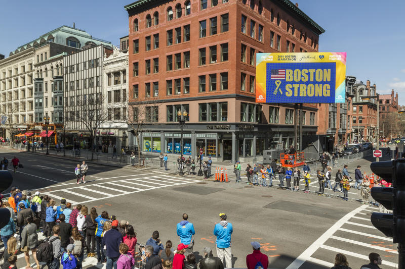 Boston Marathon billboard Boston Strong, survivor couple walks Boylston Street toward finish line where bombs exploded a year ago (Photo by Kevin Morris/Corbis via Getty Images)
