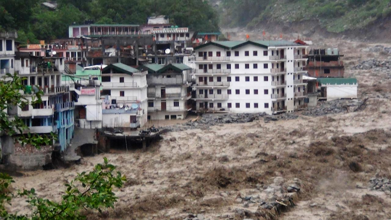 Fast moving water from the  Alaknanda river destroys building during a heavy monsoon rain in Govindghat town in the Indian state of Uttrakhand on June 17, 2013. Heavy rains lashed parts of north India Monday, resulting in the deaths of at least 18 people, as the annual monsoon covered the country nearly two weeks ahead of schedule, officials said. More than a dozen people lost their lives due to record downpours in Uttarakhand state, situated in the foothills of the Himalayas, a local official said. AFP PHOTO/ STR