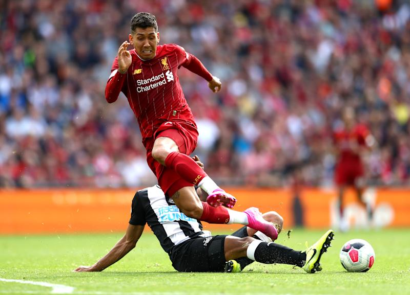 LIVERPOOL, ENGLAND - SEPTEMBER 14: Roberto Firmino of Liverpool is tackled by Isaac Hayden of Newcastle United during the Premier League match between Liverpool FC and Newcastle United at Anfield on September 14, 2019 in Liverpool, United Kingdom. (Photo by Michael Steele/Getty Images)