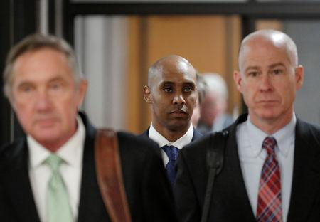 FILE PHOTO - Attorney Peter Wold, Mohamed Noor and attorney Thomas Plunkett walk out of the courthouse during a recess on the first day of opening arguments of the trial of former Minneapolis police officer Mohamed Noor in Minneapolis