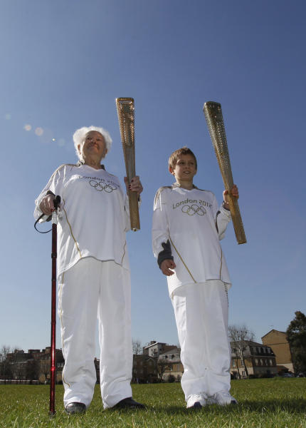 The youngest and the oldest London 2012 Olympic torch relay runners Dominic John MacGowan, right, aged 11, from Birmingham, England, and Dinah Gould , aged 99, (she will be 100 on May 23) from Harrow, London each hold a torch as they pose for the media on the day that the relay runners are announced along with the uniform that they will wear in a park in east London, Monday, March, 19, 2012. (AP Photo/Alastair Grant)