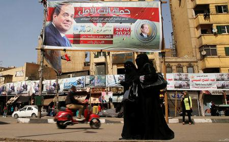 Woman wearing a full veil (niqab) walk in front of posters of Egypt's President Abdel Fattah al-Sisi during the preparations for tomorrow's presidential election in Cairo, Egypt March 25, 2018. REUTERS/Ammar Awad