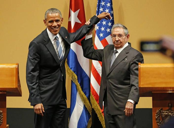 Back in March 2016, President Obama shakes hands with then-Cuban President Raul Castro, who lifts President Obama's arm after delivering speeches at the Palacio de la Revolucion in Havana.