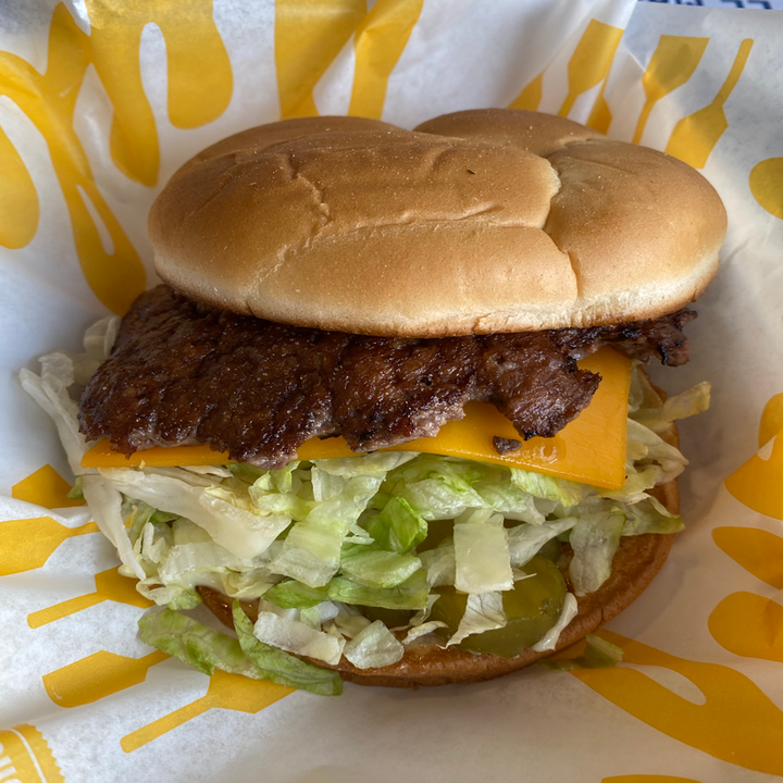 Close-up of the burger, which has a lot of lettuce and cheese under the burger patty