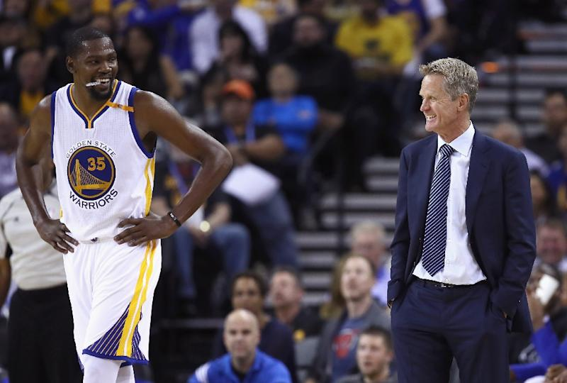 Head coach Steve Kerr of the Golden State Warriors talks to Kevin Durant during their pre-season game against the Los Angeles Clippers on October 4, 2016 in Oakland, California