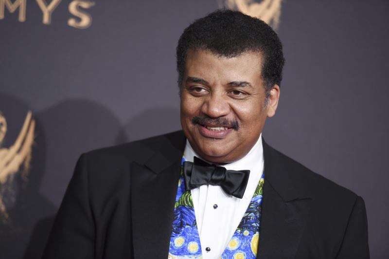 FILE- In this Sept. 9, 2017 file photo, Neil Degrasse Tyson arrives at night one of the Creative Arts Emmy Awards at the Microsoft Theater in Los Angeles. A museum spokesman said in a statement Thursday, July 25, 2019, the astrophysicist will keep his job as head of the Hayden Planetarium at New York's American Museum after the museum concluded its investigation into sexual misconduct charges against him. (Photo by Richard Shotwell/Invision/AP, File)