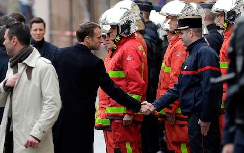 French President Emmanuel Macron (L) shakes hands with a firefighter during a visit in the streets of Paris on December 2, 2018, a day after clashes during a protest of Yellow vests (Gilets jaunes) against rising oil prices and living costs.  - Credit:  GEOFFROY VAN DER HASSELT/ AFP