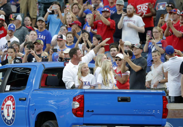 Former Texas Rangers player Josh Hamilton sits in the back of a truck with his daughters as he waves at fans after a club Hall of Fame ceremony before the team's baseball game against the Minnesota Twins in Arlington, Texas, Saturday, Aug. 17, 2019. Hamilton and former Arlington Mayor Richard Greene were inducted in the ceremony. (AP Photo/Tony Gutierrez)
