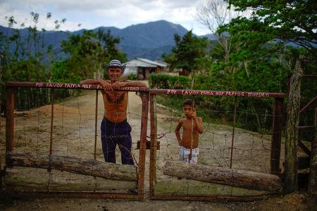 Farmer Javier Tamayo, 55, poses for a photograph with his grandson outside his home in the village of Santo Domingo, in the Sierra Maestra, Cuba, 22March 31, 2018. REUTERS/Alexandre Meneghini