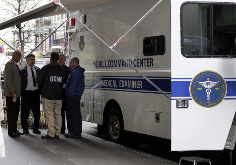 Members of the Office of the Chief Medical Examiner confer near a building in Lower Manhattan Monday, April 29, 2013, near the place where a rusted metal part from the wing of a Boeing 767 was found wedged between a mosque and an apartment building on Friday, April 26. Investigators initially thought it was part of the landing gear, because both pieces have similar hydraulics. Authorities believe the aircraft part is from one of the two hijacked planes used in the Sept. 11 attacks on the nearby World Trade Center. The medical examiner's office said Monday it is preparing the site and plans to begin sifting for human remains in the area on Tuesday, April 30. (AP Photo/Richard Drew)